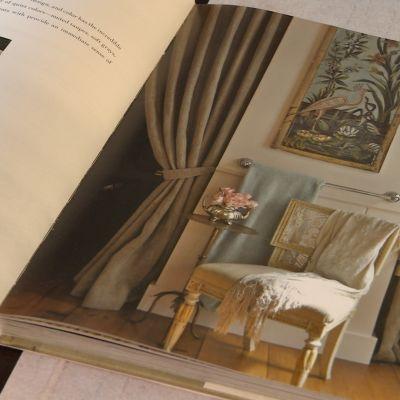 En antik stol i ett rum med beigefärgade gardiner. på väggen en tavla av en flamingo.