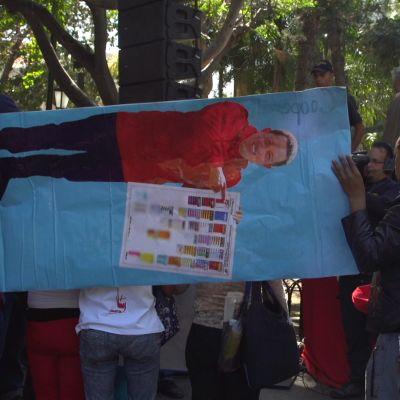 Ihmiset kannattelevat vaakatasoon käännettyä Hugo Chavezin kuvaa
