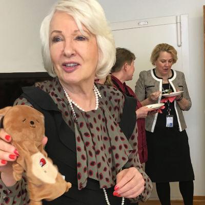 Liisa Hyssälä pitää käsissään kelapupua.