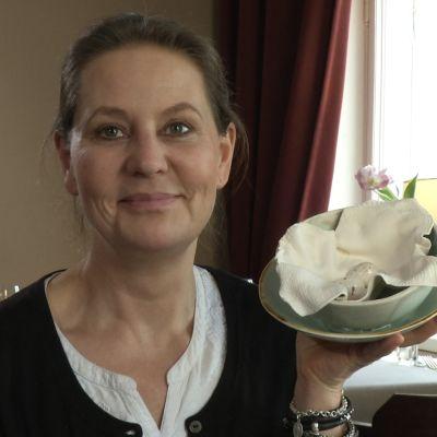 Anna Hackman håller upp sitt porslinsfat med ägg.