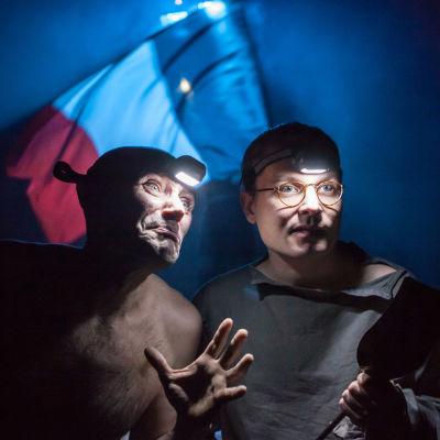 Kaksi miestä pimeässä, otsalamput otsassa, taustalla Ranskan lippu.