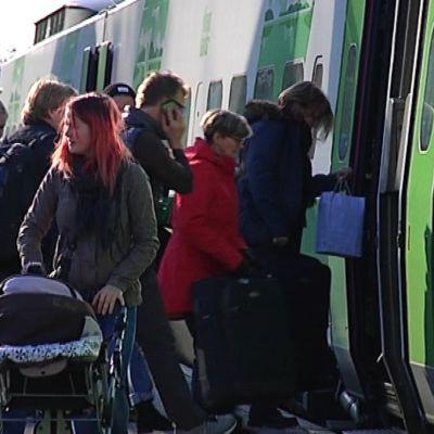 Tågresenärer stiger på ett tåg på stationen i Karis.