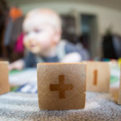 Lasten rakennuspalikoita, joiden takaa näkyy vauva.