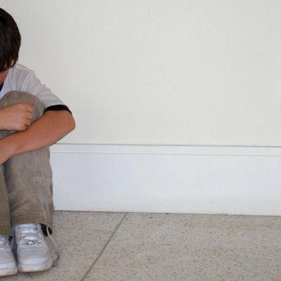Poika istuu nurkassa surullisena.