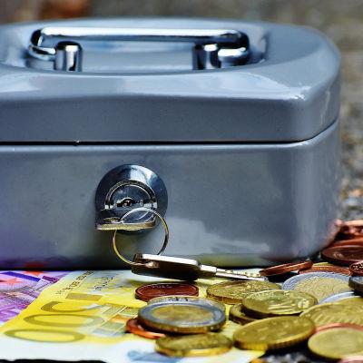 Säästölipas, kolikoita ja seteleitä kasassa.