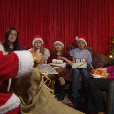 Joulupukki jakaa aattona lapsille olohuoneessa paketteja