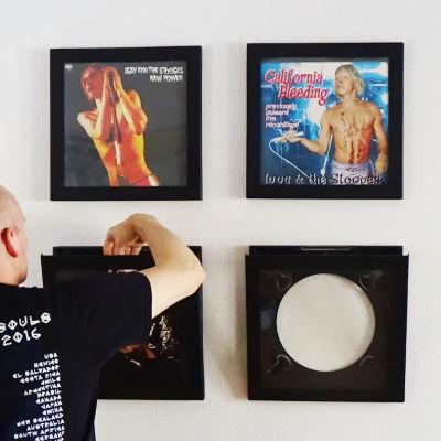 Lasse Grönroos hänger upp vinyler på väggen