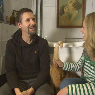 En man och en kvinna och en katt i ett badrum