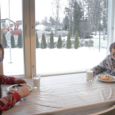 Veljekset ruokailemassa pöydän ääressä.
