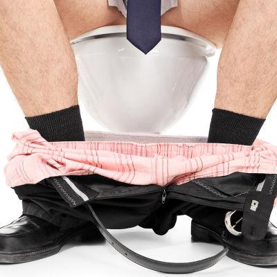 en vuxen man sitter på toaletten med byxorna nerdragna. Slipsen han har på sig hänger så att den täcker penisen