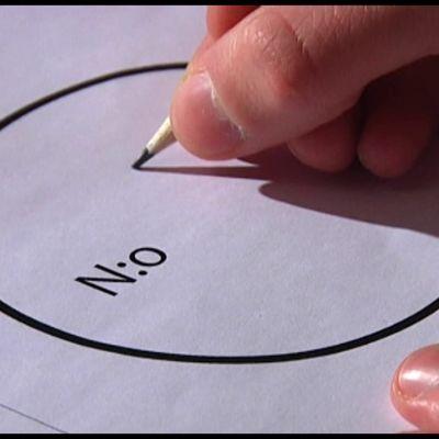 En hand som håller i en penna och är i beråd att fylla i en valsedel.