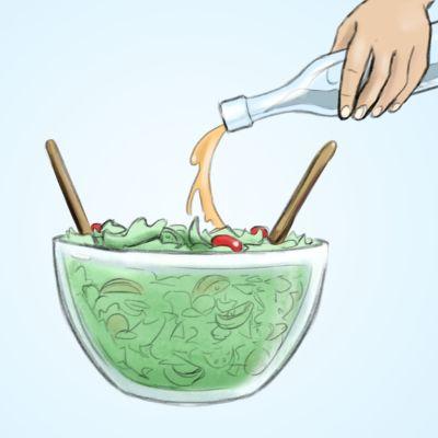 Salaatinkastiketta kaadetaan salaattikulhoon