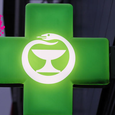 ett upplyst grönt apotekskors som är fast på en hus vägg