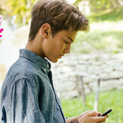 en ung pojke i puberteten som står ute i naturen och ser på sin telefon