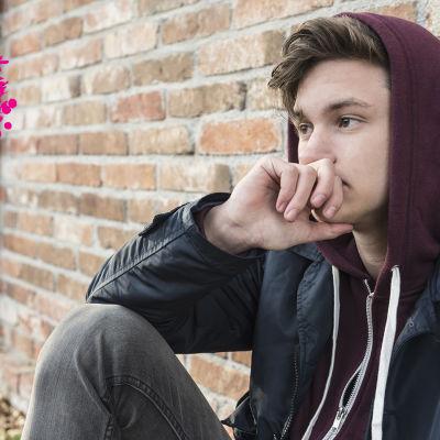 en ung man som sitter ute och lutar mot en vägg och ser bekymrad ut