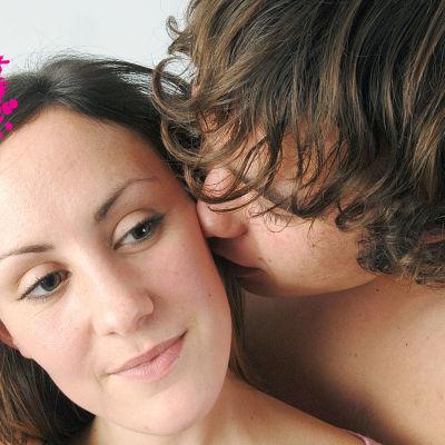 ett ungt par, en kvinna och en man som kramas och mannen pussar flickan på kinden