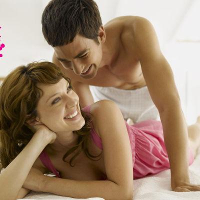 en glad man och kvinna som ligger på varandra i sängen