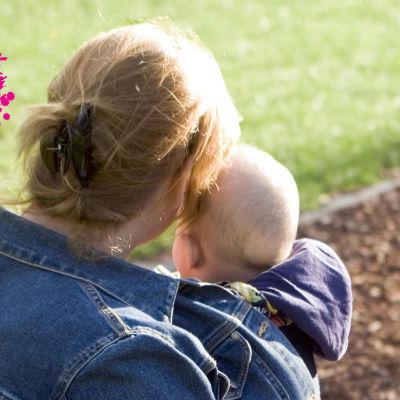 bakifrån en mamma som sitter med ett litet barn i famnen i en park