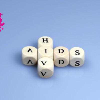 tärningar med bokstäver på, placerade så att orden hiv och aids är skrivna på en lila bakgrund