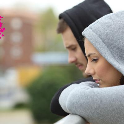 ett ungt par som är på en balkong och ser bekymarde ut