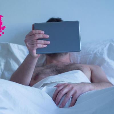 en man son rör sin penis med sin hand på täcket och ser på sin smart tablet