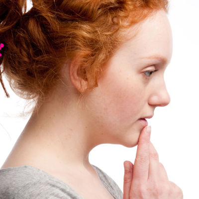 en ung kvinna som lutar sitt huvud på sin haka och ser orolig ut