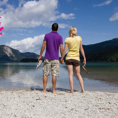 en man och en kvinna står hand i hand vid en strand