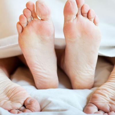 en kvinna och en man som ligger på varandra i sängen under lakan och bara fötterna syns