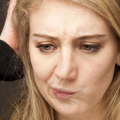 en ung kvinna som skrpar sig i huvudet och tänker