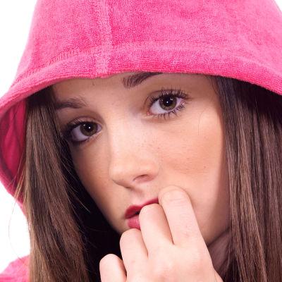 en ung kvinna som har på sig en munkjacka och ser bekymmrad ut