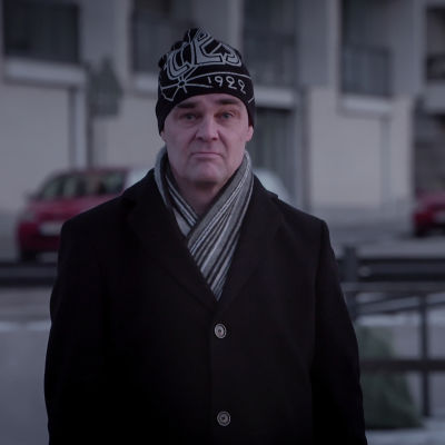 Tuhkimotarinoiden Timo seisoo talvitakki päällä ja pipo päässä. Hän katsoo suoraan kameraa kohti.