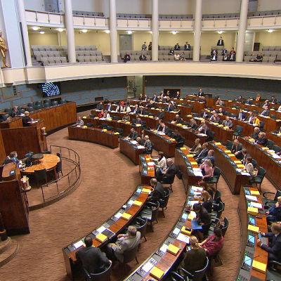 Plenisalen i riksdagshuset i Helsingfors, med ett stort antal ledamöter på plats.