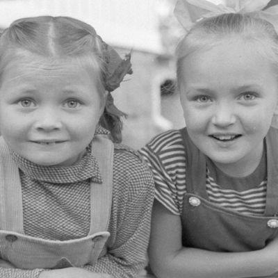 Kaksi lettipäistä tyttöä katsoo kameraan.