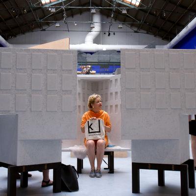 Minna Joenniemi istuu pienoismallin sisällä penkillä Venetsian biennaalissa