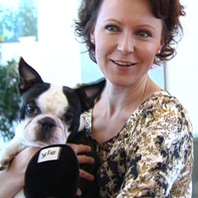 Jenni Haukio pitää Lennu-koiraa sylissä.