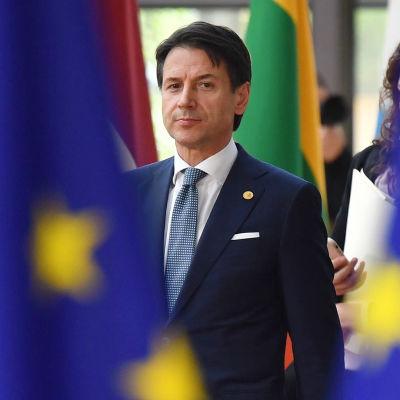 Italiens premiärminister Guiseppe Conte i bakgrunden, EU-flaggor i förgrunden.