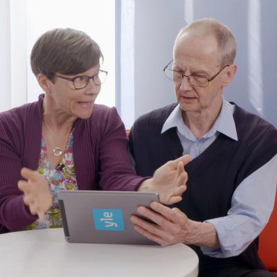 Yli-innokas digiauttaja ja hämmentynyt seniori sihvalla vierekkäin tabletti kädessä. Kuvassa Ylen toimittaja Anu Heikkinen ja Enter-yhdistyksen Ilkka Veuro.