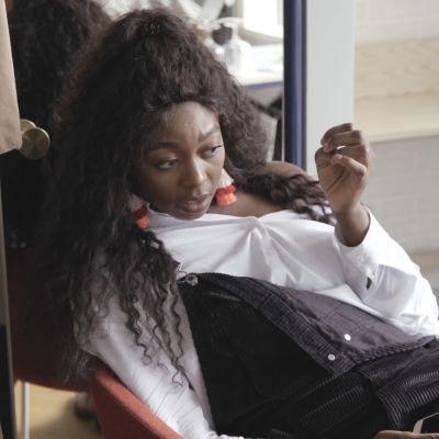 Stylisti Patisse A Lody istuu tuolilla ja pitää lepohetkeä kuvauksista.