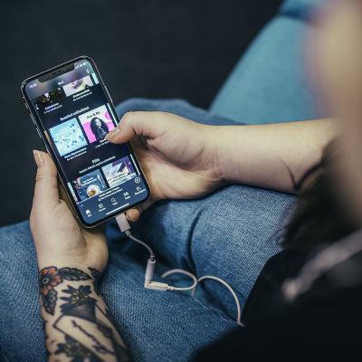 En person sitter på soffan och kollar på Spotify på sin telefon.