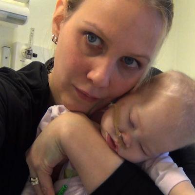Äiti kuvaa itseään ja pitää vauvaa sylissään