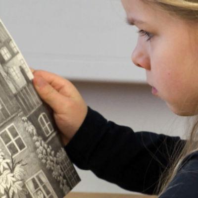 Ett barn läser en bok.