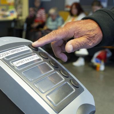 Ett finger rör könummerapparat i Kvarnbäckens hälsostation.