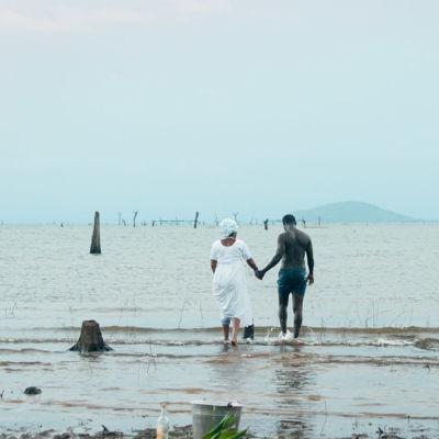 Mies ja nainen seisovat meressä käsi kädessä