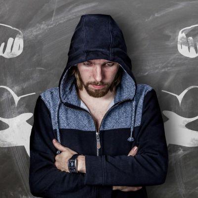 Alakuloinen mies nojaa kädet puuskassa liitutauluun, johon liidulla piirretty lihaksikkaat käsivarret.