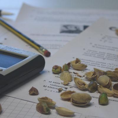 Pistaasipähkinän kuoria koepaperin päällä, laskin