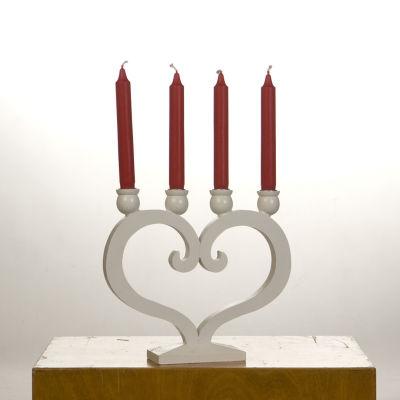 Röda adventsljus i en vit ljusstake formad som ett hjärta.