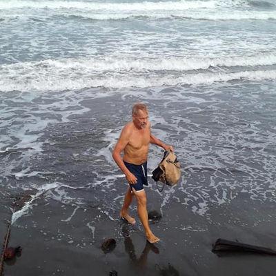 Simo Aaltonen kävelee rannalla ja kerää roskaa