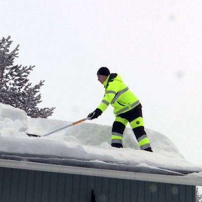 Mies kolaa lunta katolla