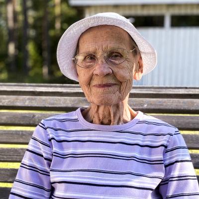 Elsa Pekkala 91 vuotta istuu kotipihassaan keinussa.