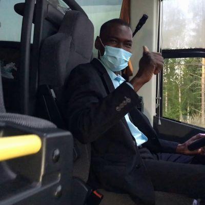 Abakar Abbas istuu bussinkuljettajan paikalla maski kasvoillaan ja näyttää peukaloa.